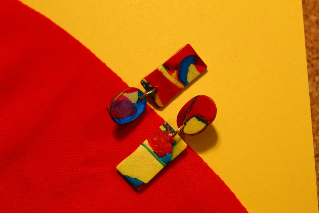 Ubumba earrings on red and yellow background